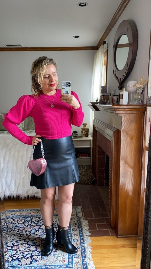 What to Wear on Valentine's Day, a blog post by Liz in Los Angeles, Los Angeles Lifestyle Blogger: an image of a blonde woman wearing a pink sweater and a leather skirt with a pink heart bag