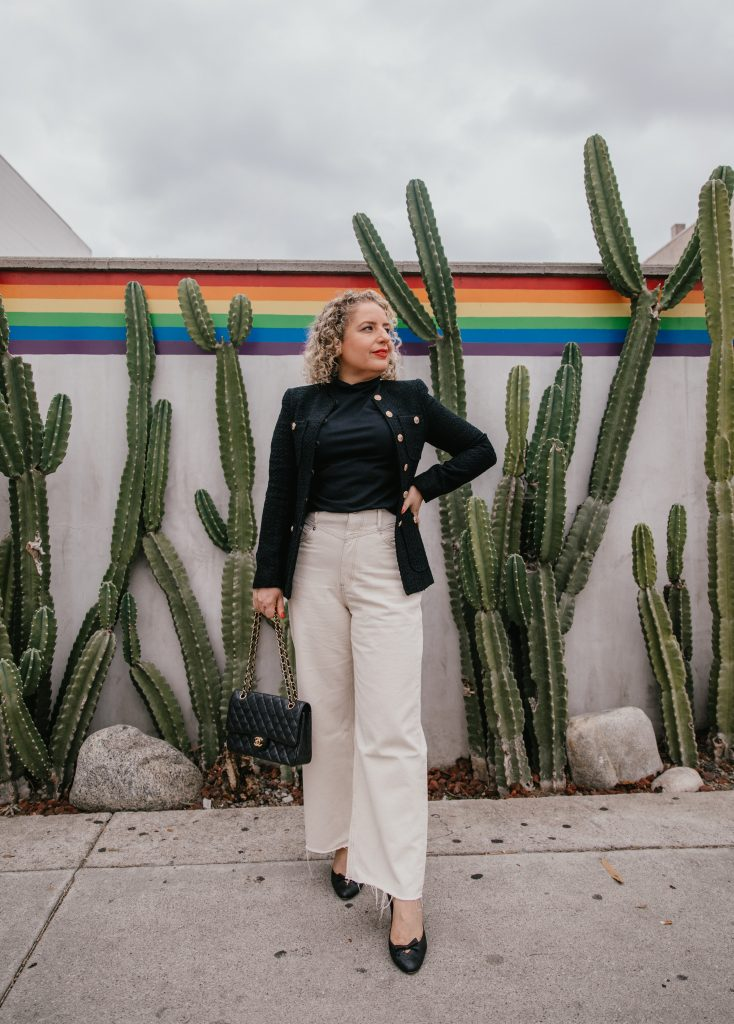 How to Choose Your First Chanel Handbag, a blog post by Liz in Los Angeles, Los Angeles Lifestyle Blogger, an image of blond women wearing a tweed black jacket and off-white wide leg jeans holding a black Chanel bag in front of cactus