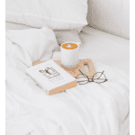 How to Reduce Stress and Sleep Better: My Complete Selfcare Routine, a blog post by Liz in Los Angeles, Los Angeles Lifestyle Blogger, an image of a latte and book on a bed