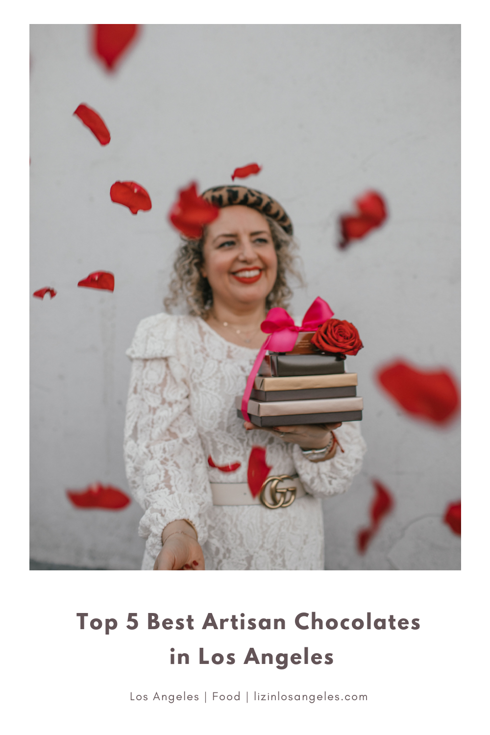 Top 5 Best Artisan Chocolates in Los Angeles, a blog post by Liz in Los Angeles, top Los Angeles blogger, an image of a blonde women wearing a white dress and animal print beret holding artisan chocolate with red roses petals flying around