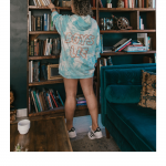 What to Wear in LA in the Spring, a blog post by Liz in Los Angeles, Los Angeles Lifestyle Blogger: an image of a blonde woman in an oversized hoodie with adiidas sneakers reaching fro a book from a bookshelf