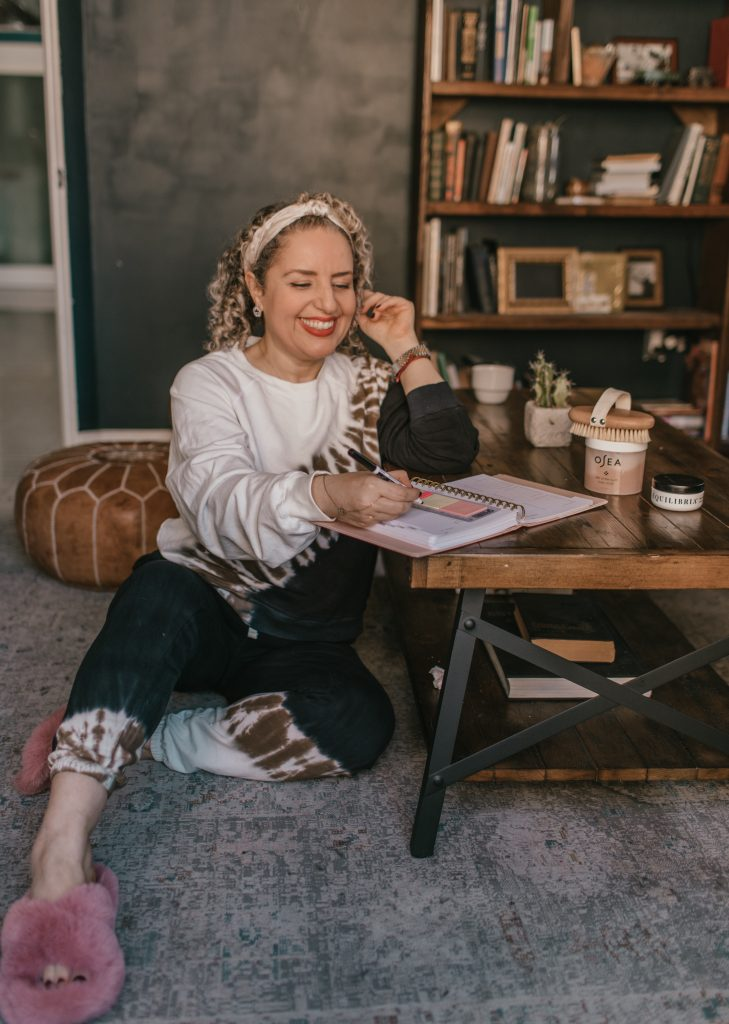 What to Wear in LA in the Spring , a blog post by Liz in Los Angeles, a top Los Angeles fashion blogger, a blonde influencer wearing a matching tie dye set in Los Angeles sitting on the floor surround by self care items