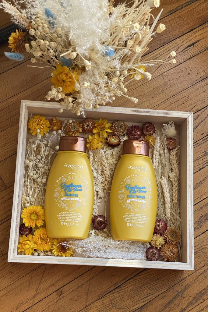 Top 10 Best Spring Beauty Essentials Women Over 30 Will Love, a blog post by Liz in Los Angeles, top Los Angeles Lifestyle Blogger, an image of a graphic of Aveeno shampoo and conditioner with flowers around them
