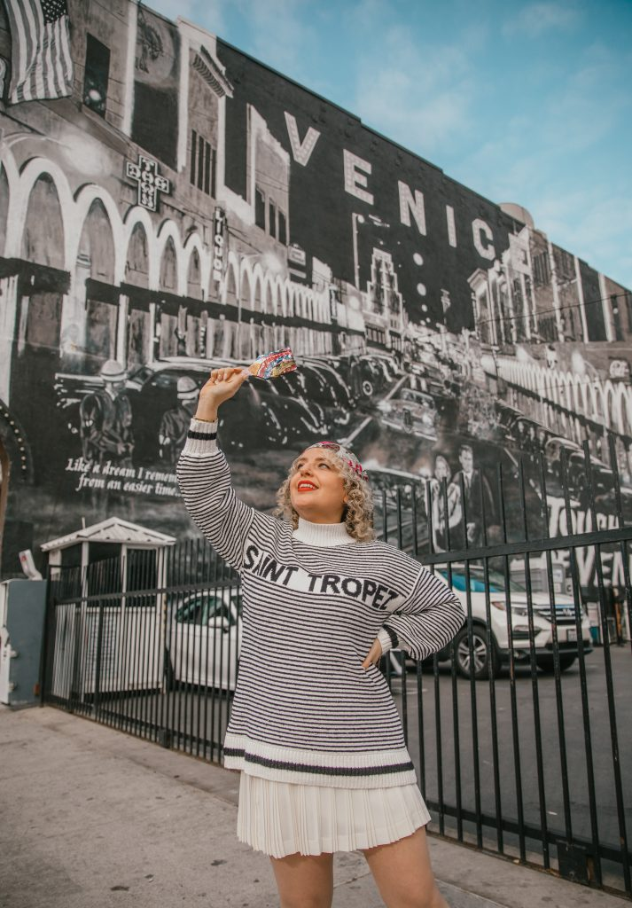 How to Celebrate Earth Day, a blog post by Liz in Los Angeles, a Los Angeles lifestyle blogger, an image of a blonde blogger wearing a strip sweater with pink scarf holding a paint brush standing in front of a wall mural on Earth Day in Venice
