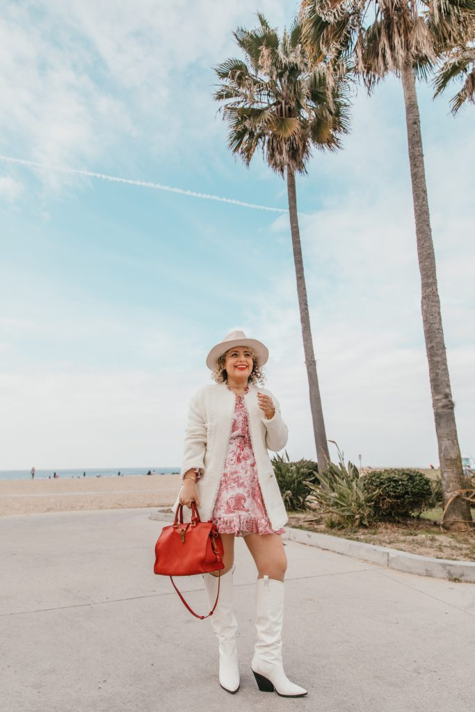Liz in Los Angeles, top Los Angeles blogger share Mido Lotto's Mido Million Giveaway: an image of a blogger standing in front of the Venice in Los Angeles wearing a red dress with a leather jacket and hat